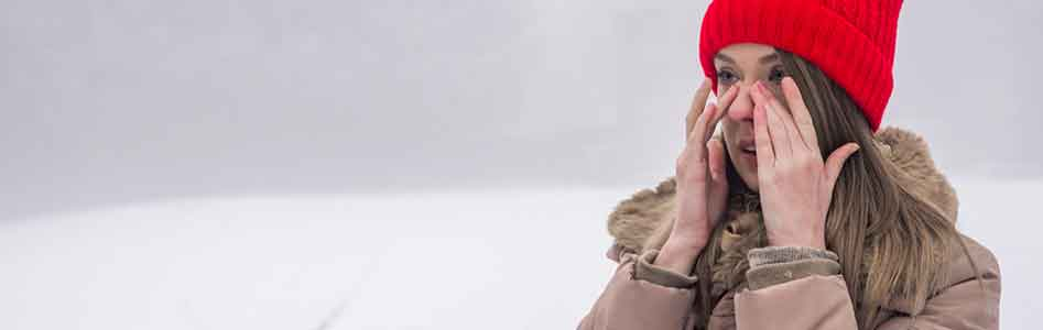 Woman having nasal congestion out in the snow